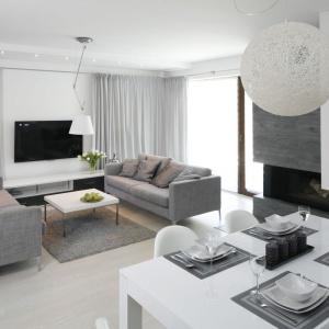 Pomieszczenie, mimo chłodnych barw jest jasne i przestronne. Efekt ten uzyskano dzięki dużym drzwiom balkonowym. Jasności dodają również lampy umieszczone w każdym pomieszczeniu.