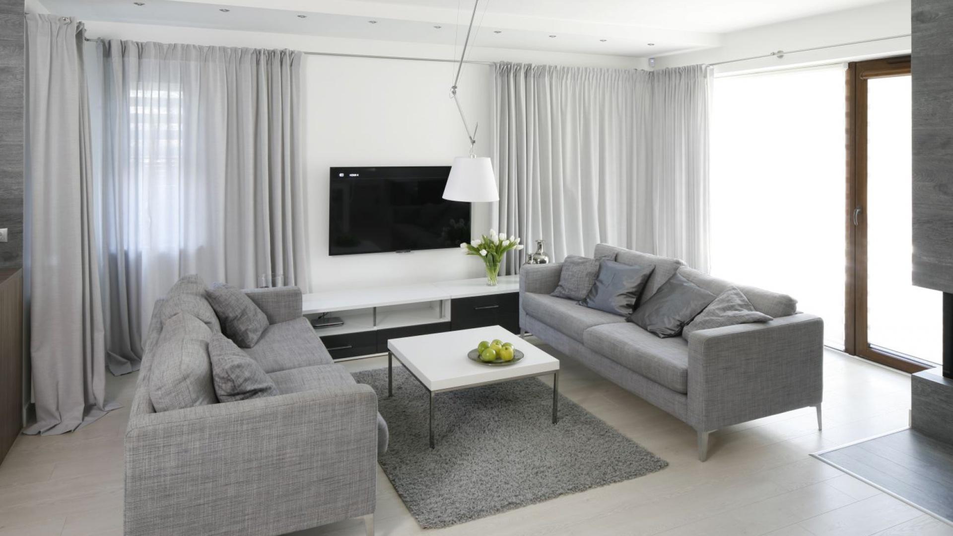 Chłodną szarość sofy i foteli w salonie podkreślono tradycyjną bielą oraz czarnymi dodatkami. Do wszystkich odcieni szarości nawiązały okienne zasłony.