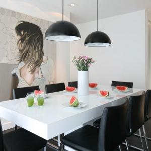 Nowoczesny stół jadalniany z grubym, białym blatem otaczają tapicerowane czarne krzesła. zestawienie tych dwóch kontrastujących kolorów połączono w postaci dwóch lamp wiszących nad stołem. Projekt: Dominik Respondek. Fot. Bartosz Jarosz.