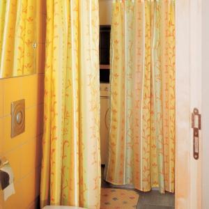Dwumetrowa łazienka z pralką i prysznicem – dwie zasłonki tworzą rodzaj kabiny, a jedna z nich także maskuje pralkę. Projekt: Dariusz Grabowski. Fot. Tomasz Markowski.