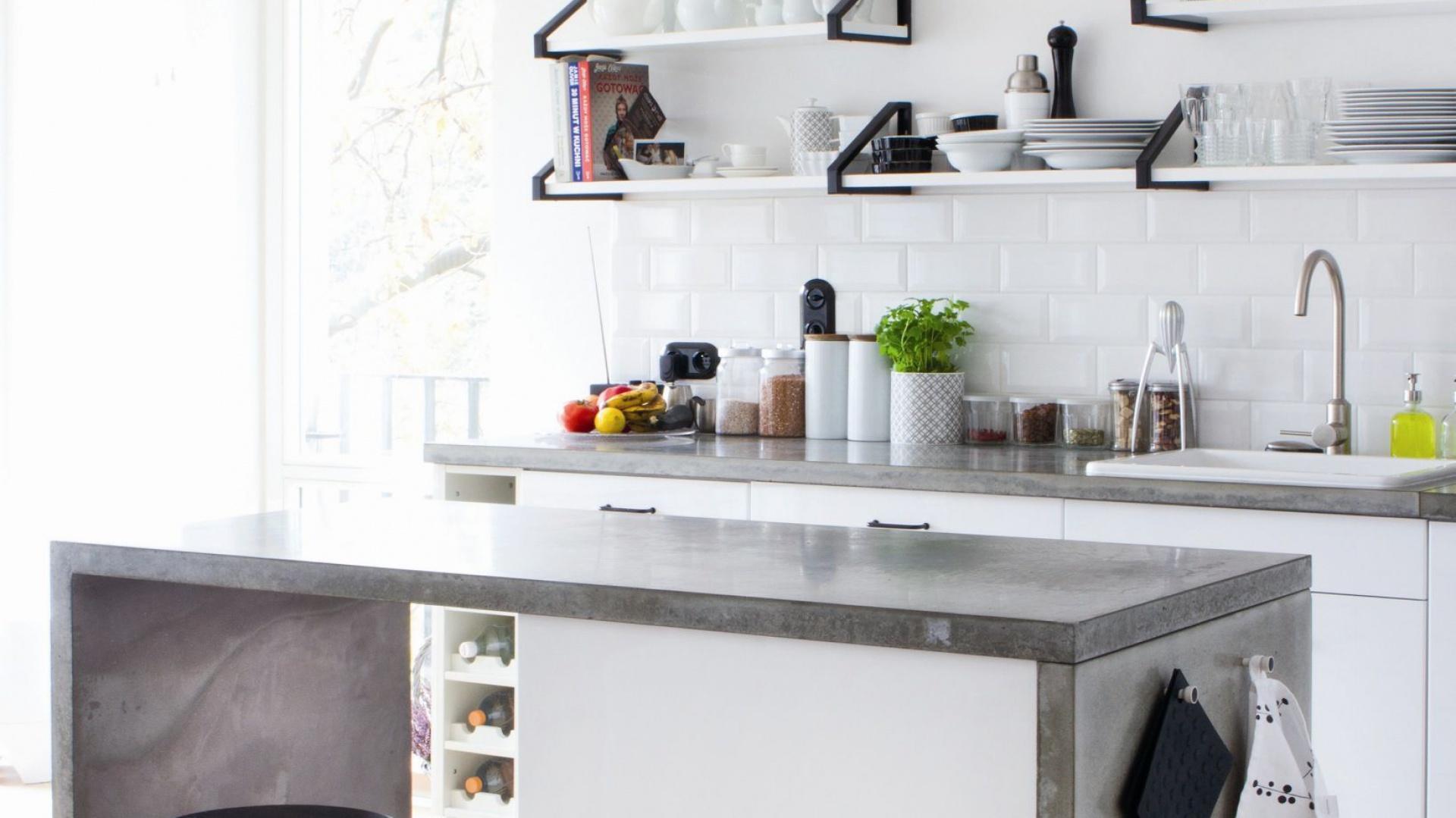 Białe meble kuchenne w tej delikatnie skandynawskiej kuchni wieńczą szare blaty wykonane z prawdziwego betonu. Fot. Morgan & Moeller.