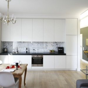 Ścianę nad blatem w tej białej kuchni wykończono fototapetą z czarno-białą komiksową grafiką. Projekt: Monika Gorlikowska. Fot. Bartosz Jarosz.