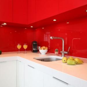 Odważna aranżacja kuchni: ścianę nad blatem pokryto czerwonym szkłem w takim samym kolorze jak górna zabudowa, z tą tylko różnicą, że szafki są matowe. Projekt: Iza Szewc. Fot. Bartosz Jarosz.