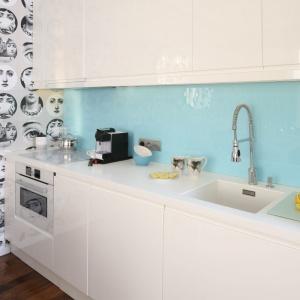 Niewielki aneks kuchenny z białą zabudowę ożywa za sprawą błękitnego lacobelu na ścianie nad blatem. Projekt: Anna Maria Sokołowska. Fot. Bartosz Jarosz.