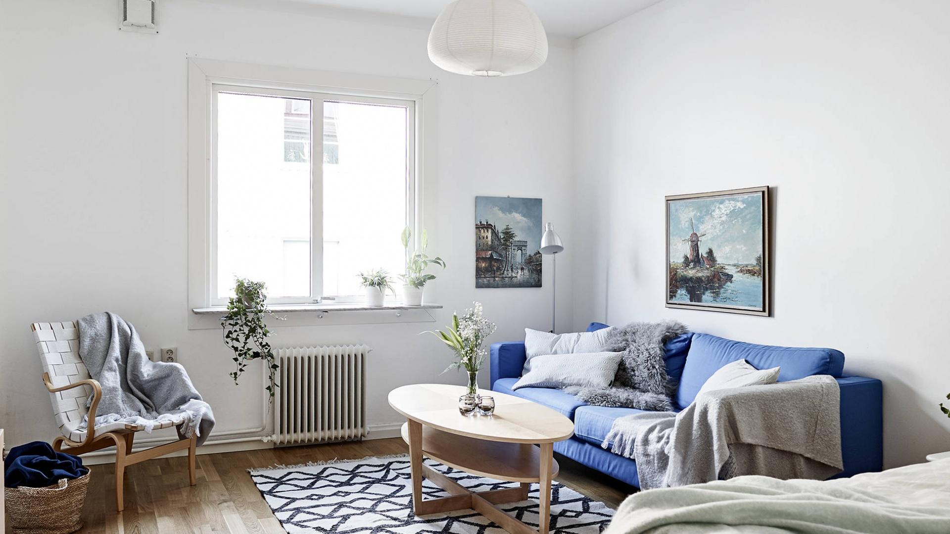 W jednym pomieszczeniu połączono salon i sypialnię, z łóżkiem sypialnianym wpasowanym w róg pomieszczenia. To jednak błękitna kanapa jest centrum całego pokoju, przykuwając wzrok i wprowadzając do wnętrza element koloru. Fot. Stadshem/Janne Olander.