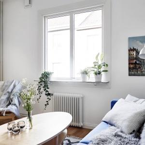 Z błękitną kanapą i dobranymi pod kolor tekstyliami harmonizują obrazy wiszące na ścianie. Fot. Stadshem/Janne Olander.