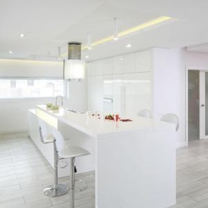 Kuchnia to królestwo bieli w wykończeniu na wysoki połysk. Zabudowa kuchenna pięknie wygląda w towarzystwie szarych ścian, pokrytych betonowym tynkiem. Zajmuje również całą ścianę, dzięki czemu zapewnia dużą ilość miejsca na przechowanie. Projekt: Dominik Respondek. Fot. Bartosz Jarosz.