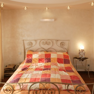 Sypialnia jest dość małych rozmiarów.  Łóżko oparte na metalowym, dekoracyjnym stelażu oraz stolik nocy na wysokich nóżkach nadają wnętrzu lekkości. Projekt: Kinga Śliwa. Fot. Bartosz Jarosz.