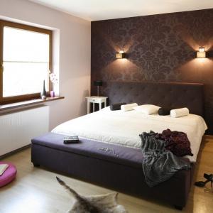 Duże tapicerowane łóżko oraz ławka nadają styl ten aranżacji. Elegancki styl wnętrza podkreślają także kinkiety emitujące światło rozproszone w dwóch kierunkach. Projekt: Jolanta Kwilman. Fot. Bartosz Jarosz.
