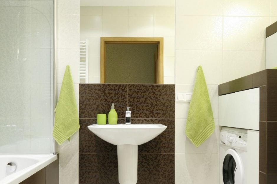 W małej łazience w bloku zmieściła się zarówno wanna z parawanem, jak i pralka. Projekt: Marta i Tomasz Kilan. Fot. Bartosz Jarosz.
