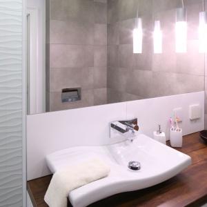 Duże lustro oraz umywalka z motywem fali to elementy, które dodają lekkości łazience w bloku. Projekt: Karolina Łuczyńska. Fot. Bartosz Jarosz.