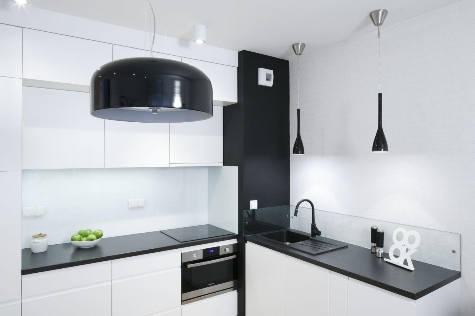 W tej czarno-białej kuchni zlewozmywak Franke utrzymano w czarnym kolorze - takim samym jak barwa blatu. Projekt: Ewa Para. Fot. Bartosz Jarosz.