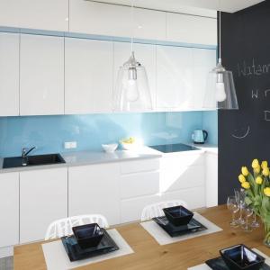 W tej kuchni białą zabudowę kuchenną ożywiono błękitnym lacobelem, a zaakcentowano mocniej czarnymi elementami w postaci AGD, zlewu oraz farby tablicowej na ścianie. Projekt: Agnieszka Zaremba, Małgorzata Kostrzewa-Świątek. Fot. Bartosz Jarosz.