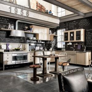 Zabudowa lodówki jak stara budka telefoniczna, metalowy okap i stylizowane meble na nóżkach budują w tej kuchni klimat minionej epoki. Fot. Marchi Cucine, kuchnia 1956.