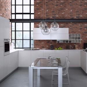 Cegła lub jej imitacje wspaniale prezentują się w towarzystwie białych nowoczesnych mebli kuchennych i wysokich, loftowych okien. W tej kuchni zamiast naturalnej cegły zastosowano cegłę dekoracyjną Loft Brick. Fot. Stone Master.