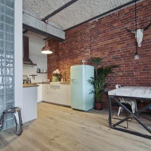 Ta loftowa kuchnia została wykończona cegłą w dwóch kolorach - na suficie białą, na ścianie - czerwoną. Surowy materiał idealnie wpisał się w industrialną stylistykę. Fot. Red Develpoment.