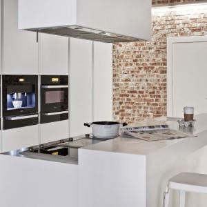 Minimalistyczne meble kuchenne w białym kolorze i matowym wykończeniu idealnie harmonizują z czerwoną cegłą na ścianie. Fot. Zajc Kuchnie.