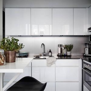 Czarny, laminowany blat wieńczy nowoczesną, białą zabudowę. Połączenie kontrastujących kolorów pięknie podkreśla szarość na ścianie nad blatem, będąca barwą pośrednią pomiędzy bielą na frontach, a czernią na blacie. Fot. Stadshem/Janne Olander.