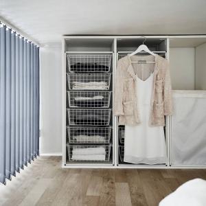 Obok łóżka, na antresoli urządzono pojemną garderobę z praktycznymi półkami w formie funkcjonalnych szuflad. Aby ewentualny nieład nie zakłócał aranżacji strefy dziennej, ta część półpiętra przesłonięta jest pionowymi żaluzjami. Fot. Stadshem/Janne Olander.