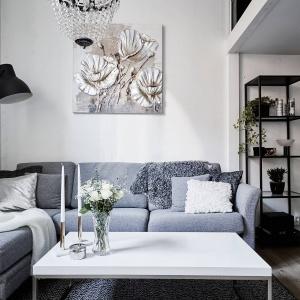 Strefa dzienna z salonem, aneksem kuchennym i niewielkim holem urządzona została na dolnym poziomie mieszkania. Salon wpasowano w róg pomieszczenia, a tworzy go elegancki, tapicerowany narożnik, stolik kawowy oraz eklektyczne oświetlenie. Fot. Stadshem/Janne Olander.