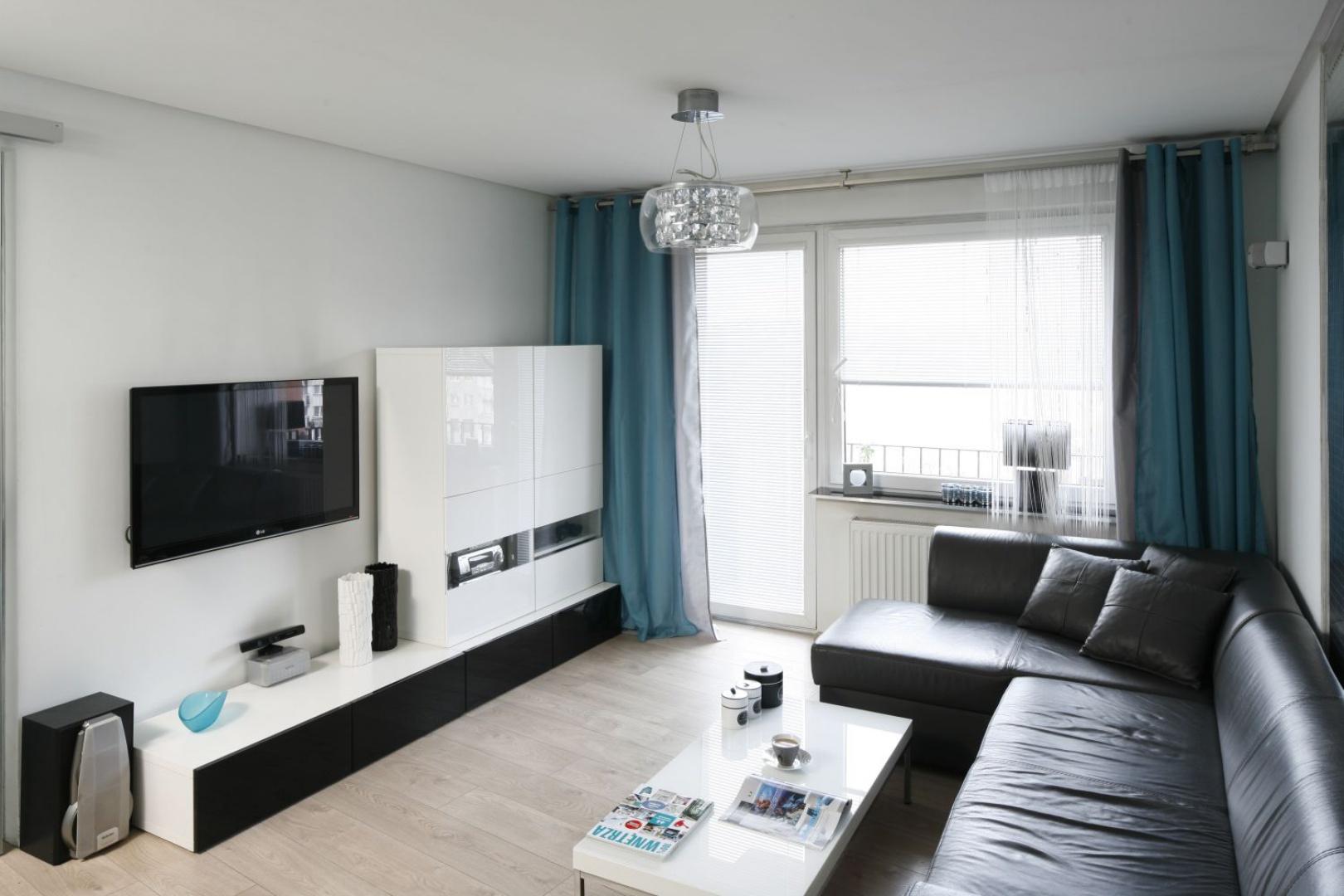 Nieduży salon urządzono w bieli i czerni. Lakierowane formy optycznie powiększają przestrzeń, turkus ożywia całość. Projekt: Marta Kilan. Fot. Bartosz Jarosz.