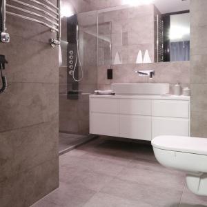 W szarej łazience wyróżnia się biała podwieszana szafka podumywalkowa wykonana na zamówienie. Projekt: Karolina Łuczyńska. Fot. Bartosz Jarosz.