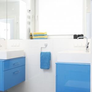 Niebieskie, podwieszane szafki to niewątpliwie oryginalna ozdoba białej łazienki. Projekt: Katarzyna Uszok-Adamczyk. Fot. Bartosz Jarosz.