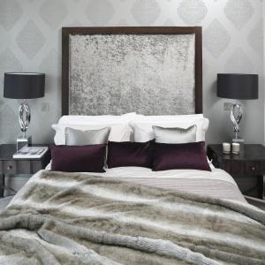 Dekoracyjny panel za łóżkiem to główny element tego wnętrza. Połyskująca tkanina w zestawieniu z dekoracyjnymi lampkami nocnymi prezentuje się bardzo elegancko. Projekt: Ventana. Fot. Bartosz Jarosz.