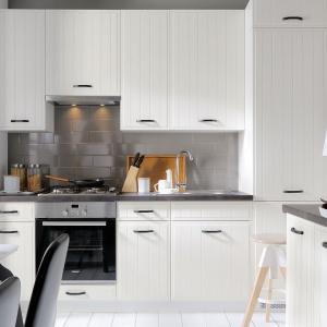 Meble kuchenne Domin z kolekcji Family Line to klasyka przeplatająca się z nowoczesnością. Białe fronty zdobią pionowe frezowania oraz kontrastujące, czarne uchwyty. Całość wieńczy szary laminowany blat. Fot. Black Red White.