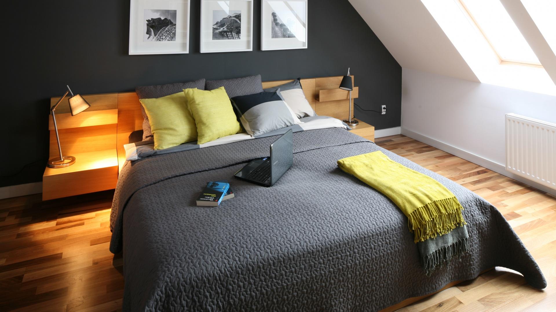 Czarna ściana za łóżkiem stanowi idealne tło dla nowoczesnego łóżka z drewnianym zagłówkiem. Projekt: Luiza Jodłowska. Fot. Bartosz Jarosz.