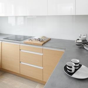 Białą kuchnię w połysku ocieplono drewnem. Blat to szary laminat. Na ścianach jest szkło, które łatwo utrzymać w czystości.