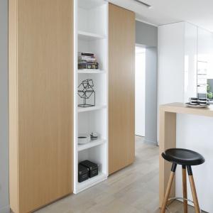Dzięki ściance, która oddziela kuchnię od korytarza i częściowo salonu, mogły powstać dodatkowe szafki oraz odkryte półki.