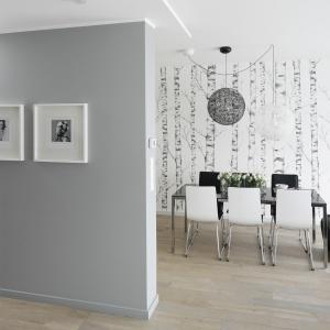 Obok nowoczesnego stołu ustawiono nietypowo zaprojektowane, tapicerowane krzesła. Rolę mocnego akcentu pełni tapeta z motywem brzózek. Jest subtelna i delikatna, ale to właśnie ona od razu po wejściu przyciąga wzrok.