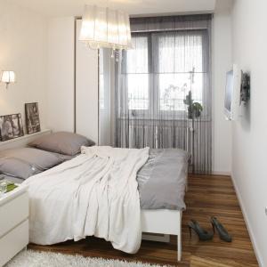 Jasna sypialnia urządzona w delikatnych bielach i szarościach. Na szczycie zagłówka umieszczono zdjęcia, które personalizują wnętrze. Projekt: Małgorzata Mazur. Fot. Bartosz Jarosz.