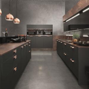 Elegancka kuchnia jest najlepszym przykładem na to, jak stylowo prezentują się czarne fronty w wykończeniu super-mat w towarzystwie miedzi. Fot. Rational Einbaukuechen, kuchnia Topaz.