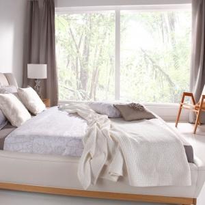 Łóżko Joy z serii Pure to elegancki mebel, którego forma zasługuje na wyeksponowanie. Miękka tkanina w ciepłym kolorze beżu nada sypialni przytulnego klimatu. Fot. Swarzędz Home.