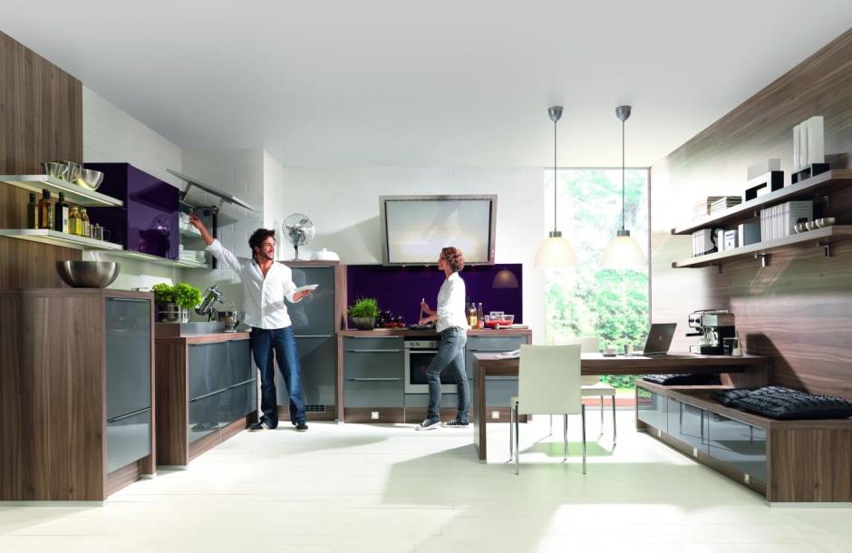 Fioletowe akcenty pięknie ożywiają zabudowę kuchenną w kolorze naturalnego drewna. Ciekawie wydzielono tu miejsce na jadalnię. Fot. Nolte Kuchen.