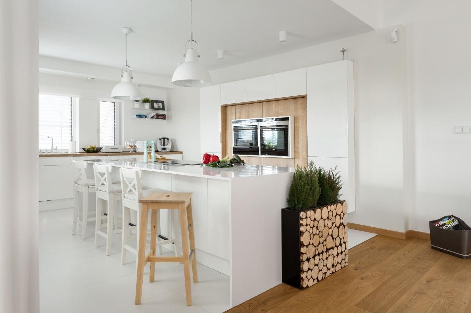 Niezwykle efektowny zabieg. Oprócz tego, że część wysokiej zabudowy wokół sprzętu AGD wykończono fornirem, wyspę kuchenną zdobi od strony salonu osobliwa donica z motywem drewnianych pieńków. Całości dopełnia wysoki drewniany stołek. Fot. Pracownia Mebli Vigo.