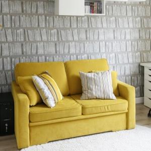 W niedużym pokoiku żółta sofa ożywia przestrzeń. Doskonale komponuje się ona z dodatkami w tym samym kolorze. Projekt: Małgorzata Mazur.