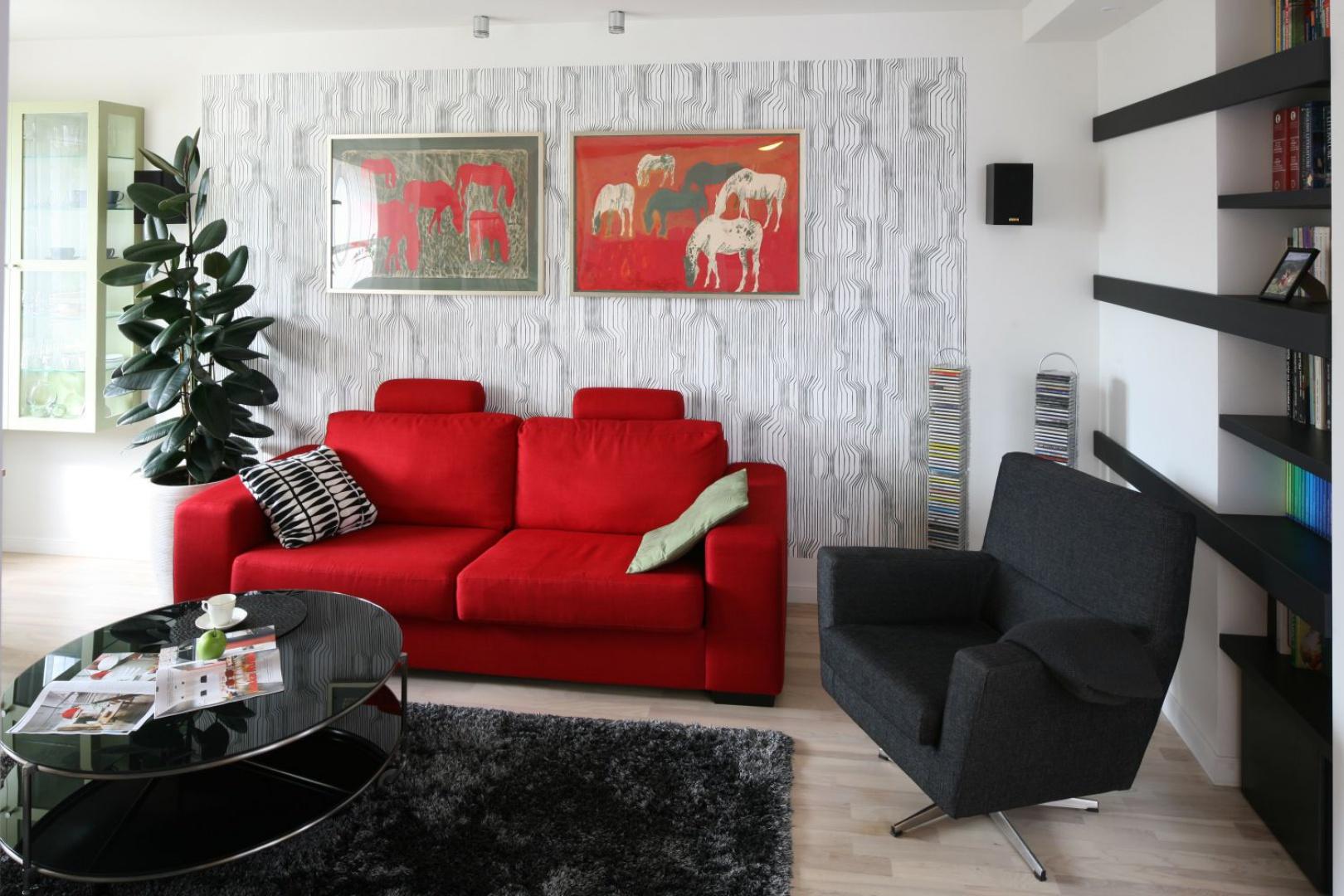 Klimat tego salonu to zasługa świetnie skomponowanych kolorów. Rządzą tu czernie i biele, na tle których czerwona dwuosobowa kanapa stanowi mocny stylistycznie akcent. Projekt Marta Kruk. Fot. Bartosz Jarosz.