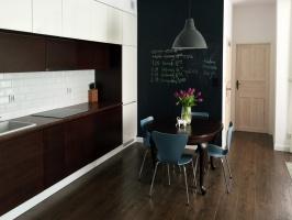 W tym wnętrzu nic nie jest przypadkowe. Stół, podłogę i meble kuchenne łączy ten sam kolor drewna,  ale dzięki wymieszaniu stylów nie jest nudno i bezpłciowo.