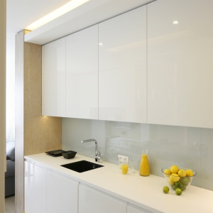 Ściana jest wykończona lakierowanym szkłem, łatwym do czyszczenia. Pod białym blatem zainstalowano podwieszany zlewozmywak w kontrastowym,  czarnym kolorze.