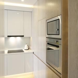 Wysoka zabudowa, m.in. z piekarnikiem, mikrofalówką oraz lodówką, znajduje się przy wejściu do mieszkania.