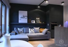Ceglana czarna ściana przechodząca w zabudowę kuchenną jest najmocniejszym akcentem salonu i to ona nadaje charakteru całemu wnętrzu.