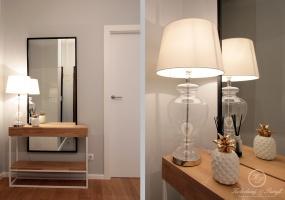 Na wejściu do mieszkania wita nas metalowa konsola z dużym lustrem i delikatną lampą.