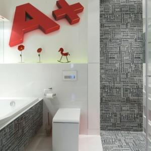 Płytki z nadrukami liter świetnie dekorują ścianę w strefie prysznica. Projekt: Katarzyna Mikulska-Sękalska. Fot. Bartosz Jarosz.
