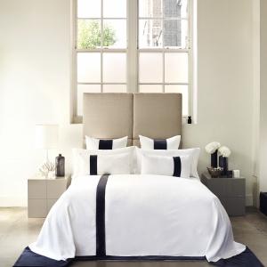 Minimalistyczne wnętrza lubią również proste stylistycznie dodatki. Biała pościel z cienkim czarnym pasem będzie doskonałym uzupełnieniem minimalistycznego wnętrza. Fot. Kellyhoppen.