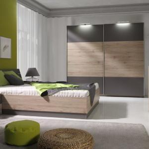 Jasne drewno i szarości to wyjątkowo ciekawe połączenie w kolekcji Dione. Szafa dodatkowo oświetlona u góry nada sypialni wyrafinowanego smaku. Cena łóżka 1.019 zł. Fot. Maridex.