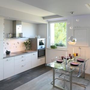 Miejsce na jadalnię wydzielono tuż przy kuchni. Szklany stół i krzesła ustawione przy ścianie są praktycznie niewidoczne, więc doskonale wtapiają się w jasną przestrzeń. Projekt: Arkadiusz Grzędzicki. Fot. Bartosz Jarosz.