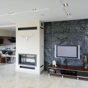 Telewizor w salonie powieszono na ścianie wyłożonej eleganckim kamieniem w czarno-szarej tonacji kolorystycznej. Projekt: Piotr Stanisz. Fot. Bartosz Jarosz.
